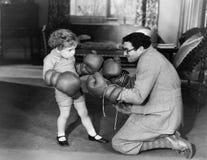使用与拳击手套的父亲和年轻儿子(所有人被描述不更长生存,并且庄园不存在 供应商warran 免版税库存照片
