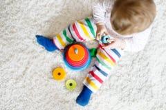 使用与教育五颜六色的木rainboy玩具金字塔的可爱的逗人喜爱的美丽的矮小的女婴 免版税库存照片
