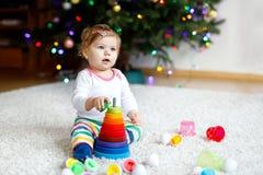 使用与教育五颜六色的木rainboy玩具金字塔的可爱的逗人喜爱的美丽的矮小的女婴 库存照片