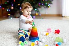 使用与教育五颜六色的木rainboy玩具金字塔的可爱的逗人喜爱的美丽的矮小的女婴 免版税图库摄影