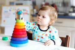 使用与教育木彩虹玩具金字塔的可爱的逗人喜爱的美丽的矮小的女婴 库存图片