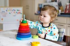 使用与教育木彩虹玩具金字塔的可爱的逗人喜爱的美丽的矮小的女婴 免版税库存图片