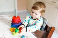 使用与教育木彩虹玩具金字塔的可爱的逗人喜爱的美丽的矮小的女婴 免版税库存照片