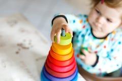 使用与教育木彩虹玩具金字塔的可爱的逗人喜爱的美丽的矮小的女婴 库存照片