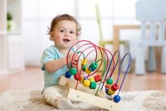 使用与教育玩具的婴孩在托儿所 免版税库存照片