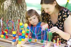 使用与教育玩具的小女孩和母亲 免版税库存照片