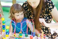使用与教育玩具的小女孩和母亲 库存照片