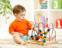 使用与教育玩具的滑稽的孩子室内 库存照片