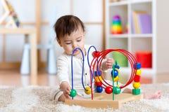 使用与教育玩具的滑稽的孩子室内 免版税库存图片