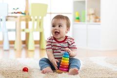使用与教育金字塔的小孩子在家戏弄 小孩获得乐趣户内 免版税库存照片