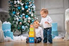 使用与木字母表块的两个兄弟反对圣诞树 免版税库存图片