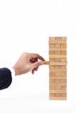 使用与木比赛(jenga)的商人手 免版税库存照片