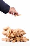 使用与木比赛(jenga)的商人 在白色backgro 免版税图库摄影
