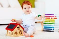 使用与木玩具,数字的逗人喜爱的红头发人婴孩,学会计数 免版税库存图片