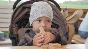 使用与木立方体的小孩男孩在咖啡馆的一张桌上 股票录像