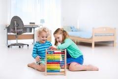 使用与木算盘的孩子 培训玩具 免版税库存照片