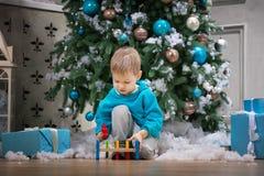使用与木锤子玩具的男孩,当坐在圣诞树旁边时 免版税图库摄影