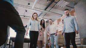 使用与橄榄球在办公室,慢动作低角度的男性腿特写镜头  愉快的同事享受体育活动 股票视频