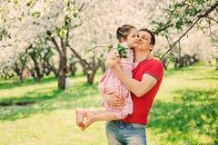 使用与步行的孩子女儿的愉快的父亲在春天 图库摄影