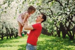 使用与步行的小孩女儿的愉快的父亲在春天 库存照片