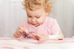 使用与母亲修指甲化妆用品的逗人喜爱的婴孩 免版税库存图片