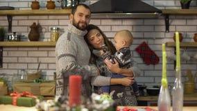 使用与母亲胳膊的婴孩小儿子的温暖的毛线衣的有胡子的父亲在厨房里 人给胡椒丸子羹孩子 股票视频