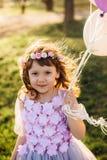 使用与气球的一件美丽的紫色礼服的女孩在公园 免版税库存图片