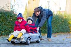 使用与汽车的两个小孩男孩和父亲,户外 免版税库存照片