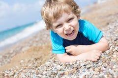使用与沙子和石头的小小孩男孩在海滩 免版税库存照片