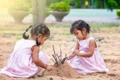 使用与沙子的儿童两亚裔小女孩在操场 免版税库存图片