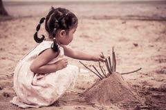 使用与沙子的儿童亚裔逗人喜爱的小女孩在操场 免版税库存图片
