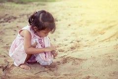 使用与沙子的儿童亚裔逗人喜爱的小女孩在操场 库存图片