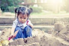 使用与沙子的儿童逗人喜爱的小女孩在操场 图库摄影