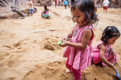 使用与沙子的儿童逗人喜爱的小女孩在操场 免版税库存照片