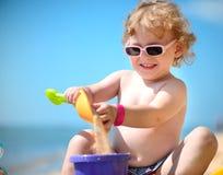 使用与沙子的太阳镜的逗人喜爱的小女孩 免版税库存图片