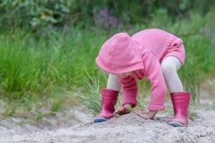 使用与沙子的学龄前儿童女孩在夏天森林里 免版税库存图片