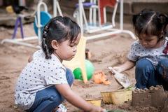 使用与沙子的孩子在操场 库存图片