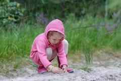 使用与沙子的小女孩在夏天森林里 图库摄影