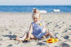 使用与沙子的愉快的子项在海滩在夏天 库存照片