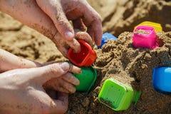 使用与沙子的父亲和婴孩手在海滩 免版税库存照片