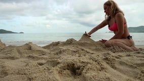 使用与沙子的美丽的亭亭玉立的妇女在异乎寻常的海滩 股票视频