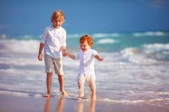 使用与沙滩的小辈兄弟的年轻男孩 库存照片