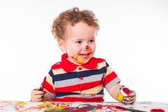 使用与油漆的逗人喜爱的愉快的男婴 库存图片