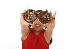 使用与油炸圈饼的红色礼服的孩子在她的拿着他们的手上在最前面微笑愉快 免版税图库摄影