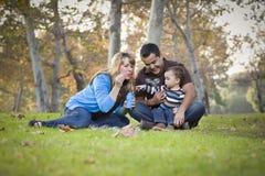 使用与泡影的愉快的混合的族种种族家庭在公园 免版税图库摄影