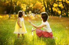 使用与泡影的母亲和女儿 免版税库存图片
