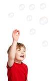 演奏泡影的逗人喜爱的男孩 免版税库存照片