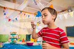 使用与泡影鞭子的逗人喜爱的男孩在生日聚会期间 免版税库存图片