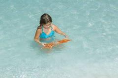 使用与海星的孩子在天蓝色的透明的平静的海洋 图库摄影