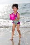 使用与海滩玩具的亚裔矮小的中国女孩 免版税库存照片